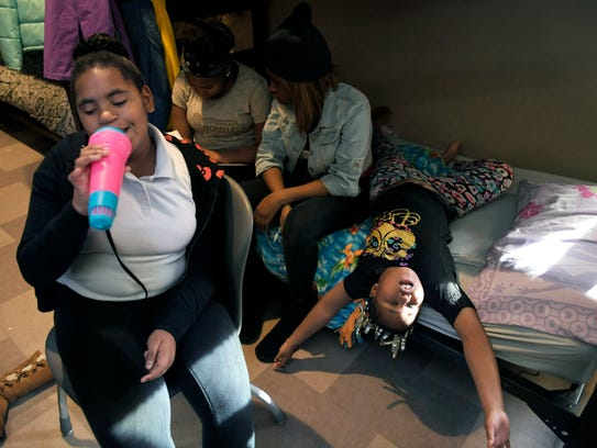 Emya Washington, left,  sings on a toy microphone while