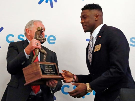Ole Miss wide receiver A.J. Brown, right, is handed the Conerly Trophy that he was awarded for Mississippi's top college football player, by Bill Blackwell, executive director of the Mississippi Sports Hall of Fame and Museum, during a ceremony in Jackson, Miss., Tuesday, Nov. 28, 2017. (AP Photo/Rogelio V. Solis)