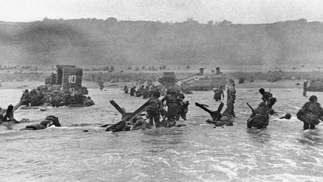 Some of the first assault troops to hit the Normandy, France beachhead take cover behind enemy obstacles to fire on German forces as others follow the first tanks plunging through the water toward the German-held shore June 6, 1944, during World War II.