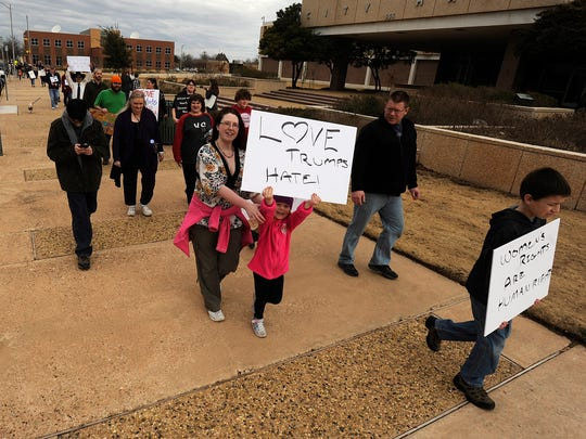 People march around Abilene City Hall during the Women's