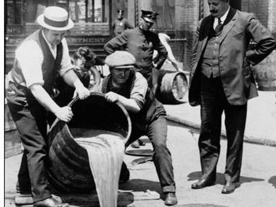 Law enforcement officials pour whiskey down the drain during prohibition.