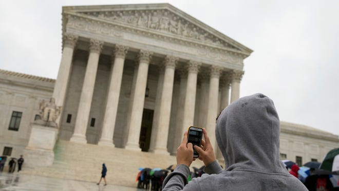 FILE - This April 29, 2014 file photo shows a Supreme Court visitor using his cellphone to take a photo of the court in Washington. A unanimous Supreme Court says police may not generally search the cellphones of people they arrest without first getting search warrants. The justices say cellphones are powerful devices unlike anything else police may find on someone they arrest.  (AP Photo, File)
