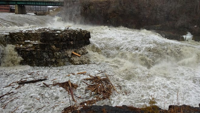 The Winooski River, seen here from the overlook by the Winooski One Hydro Plant, roars along on Thursday afternoon, carrying with it chunks of ice, tree branches and tree trunks.