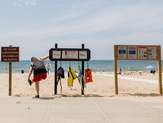 A pedestrian uses a Life Jacket Loaner Station as support