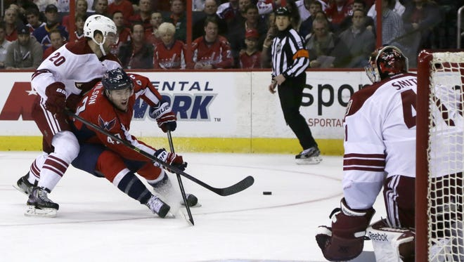 Washington Capitals right wing Tom Wilson (43) tries to shoot the puck as he struggles with Coyotes defenseman Chris Summers on March 8, 2014.