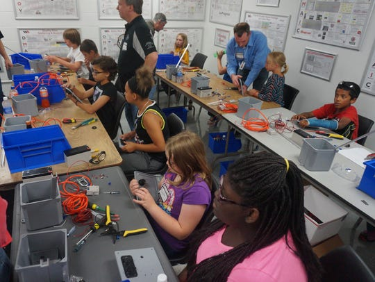Students sit at their workstations, assembling light.
