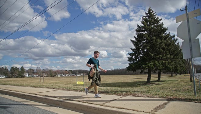 A pedestrian walks down East Chestnut Hill Road by the former Our Lady of Grace Home. New Castle County is looking at the possibility of spending millions to purchase at least a portion of a former orphanage property.