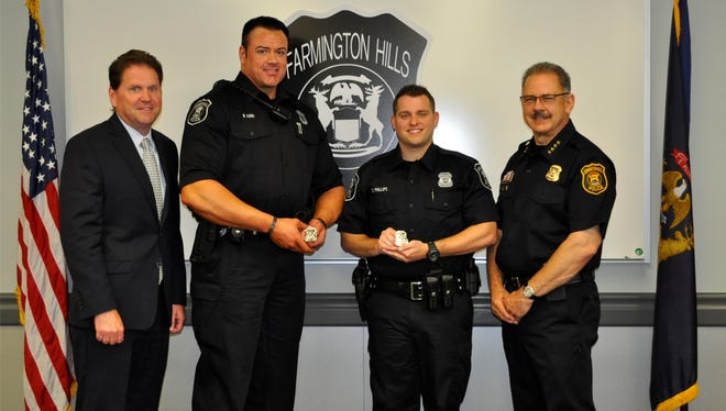Farmington Hills City Manager Dave Boyer (from left) with Officers Nicholas Tiano and Zachariah Phillips, and Chief of Police Charles Nebus.