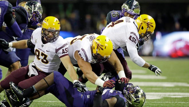 Washington's Keishawn Bierria, bottom, is knocked down by Arizona State's Kody Kohl (83) and Vi Teofilo as Demario Richard carries in the second half of an NCAA college football game Saturday, Oct. 25, 2014, in Seattle. Arizona State won 24-10.