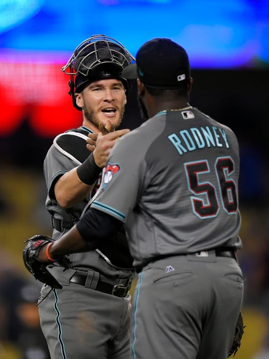 Arizona Diamondbacks catcher Chris Iannetta, left, and relief pitcher Fernando Rodney congratulate each other after the Diamondbacks defeated the Los Angeles Dodgers 3-1 in a baseball game, Tuesday, Sept. 5, 2017, in Los Angeles. (AP Photo/Mark J. Terrill)