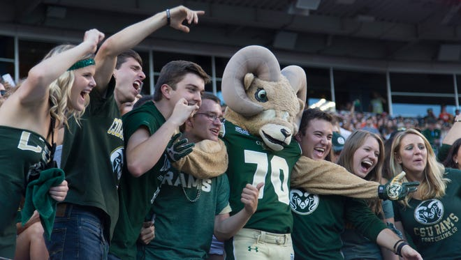 CSU football fans and the school's mascot, CAM the Ram, pose for TV cameras during last year's Rocky Mountain Showdown football game at Sports Authority Field at Mile High in Denver. The NFL stadium allows fans to bring in outside food and factory-sealed beverages, which are banned at CSU's new stadium, but won't sell beer at Friday night's game.
