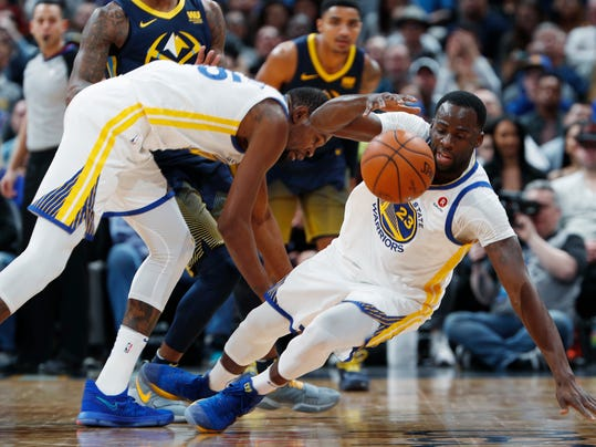 Golden State Warriors forward Kevin Durant, left, collides with forward Draymond Green, who tries to pick up a loose ball during the second half against the Denver Nuggets in an NBA basketball game Saturday, Feb. 3, 2018, in Denver. The Nuggets won 115-108. (AP Photo/David Zalubowski)
