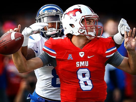 University of Memphis defender Arthur Maulet (back) knocks the ball away from SMU quarterback Ben Hicks (front), causing a fumble, during first quarter action at Gerald J. Ford Stadium in Dallas Saturday. Memphis recovered the ball and scored a touchdown on the drive.