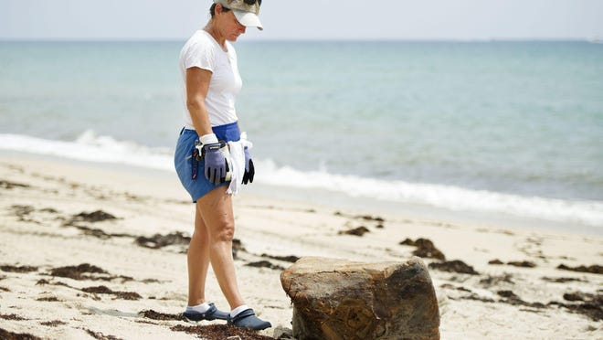 Diane Buhler of Friends of Palm Beach stands near a large piece of oily debris just off Blossom Way Tuesday August 4, 2020 in Palm Beach.