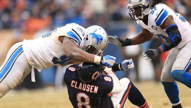 Detroit Lions defensive end Ezekiel Ansah (94) hits Chicago Bears quarterback Jimmy Clausen (8) in the helmet and is called for a personal foul during the fourth quarter at Soldier Field.