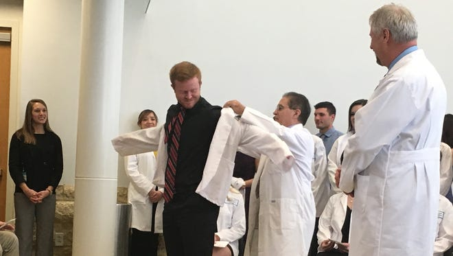 Hunter Hensley receives his white coat from Academic Director Don Solimini as Dr. David Paulk, the school's physician assistant program director, looks on.