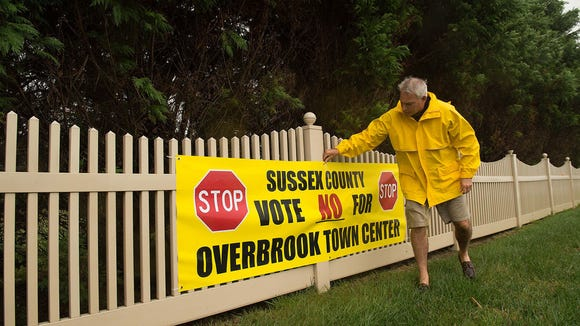Rich Borrasso straightens a sign that advocates voting 'No' for the Overbrook Town Center, which would be across from the Red Fox Fun development in Milton.