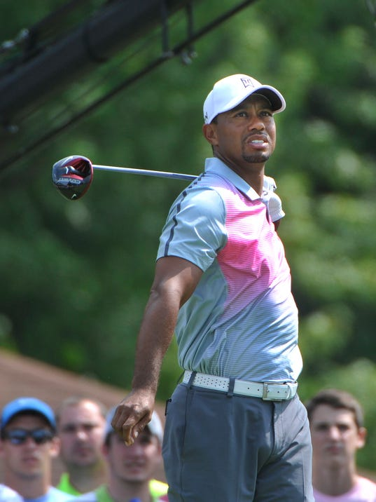 Tiger Woods watches his tee shot on the eighth hole, during the first round of the Bridgestone Invitational golf tournament, Thursday, July 31, 2014, in Akron, Ohio. (AP Photo/Phil Long)