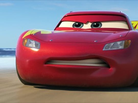 "Character Lightning McQueen driving on a beach in Disney's ""Cars 3."""