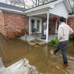 Gregory Shuford, left, and Terease Shuford keep an eye on flooding in west Montgomery, Ala. as they prepare for  Christmas on Friday December 25, 2015.