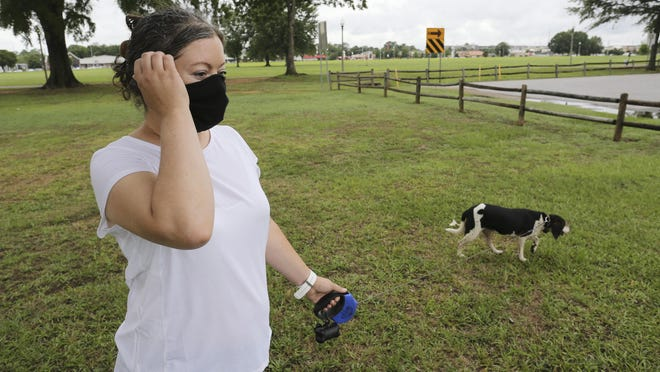Jennie Killough wears her face mask as she walks her dog, Becky, in Snow Hinton Park on Wednesday. Killough said she would support an ordinance requiring people to wear a face mask in public. The Tuscaloosa City Council is now considering such a law and is expected to vote on the matter next week.
