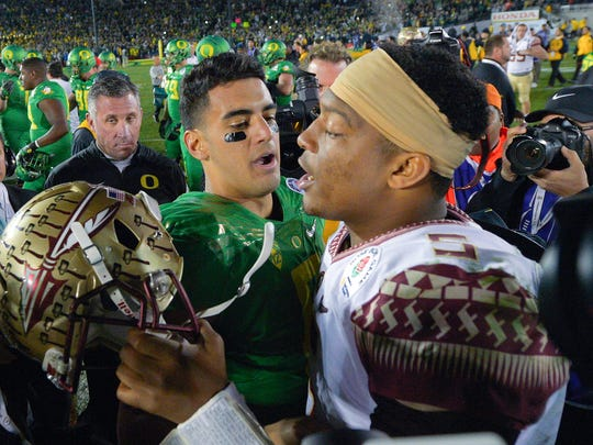 FILE - In this Jan. 1, 2015, file photo, Oregon quarterback Marcus Mariota, center left, greets Florida State quarterback Jameis Winston after Oregon's win in the Rose Bowl NCAA college football playoff semifinal game in Pasadena, Calif.