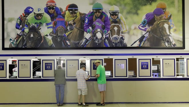 Fans place bets ahead of the running of the Black-Eyed Susan horse race at Pimlico race course in Baltimore.
