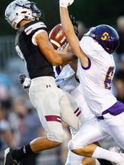 Ankeny Centennial High School's Jake Pinegar (8) tries to catch a pass as he is guarded by Johnston's Sam Nielsen (6) in the second half Friday, Aug. 25, 2017, during their game in Ankeny.
