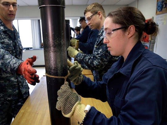 Ensign Megan Stevenson, right, of Raymond, Maine, trains at patching high-pressure pipe leaks during a class at the Naval Submarine School, in Groton, Conn. The Navy said Tuesday, July 10, 2018, it will let women sailors sport ponytails and other longer hairstyles, reversing a policy that long forbade females from letting their hair down.
