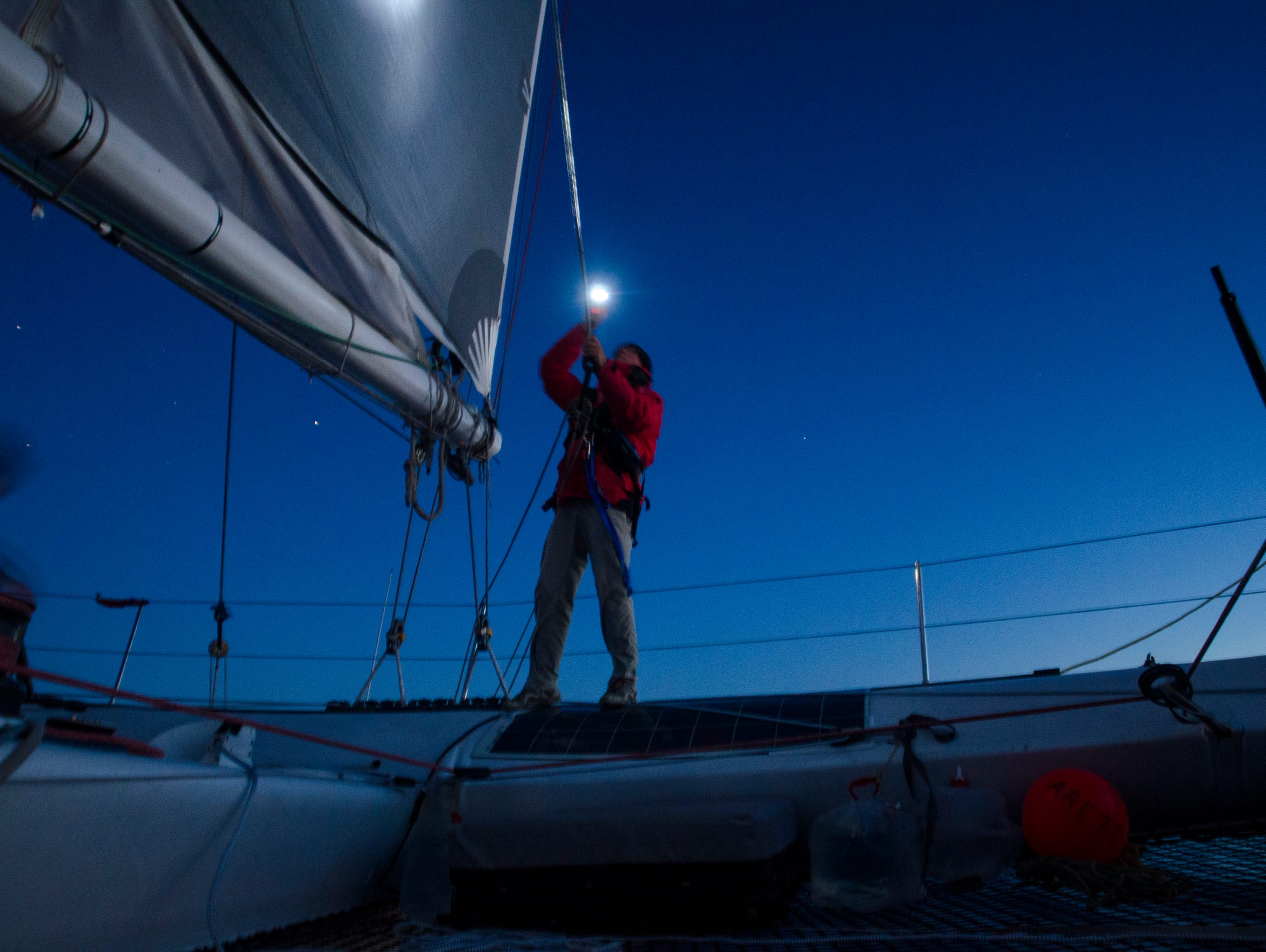 Arete Skipper Rick Warner checks a sail at night Saturday,