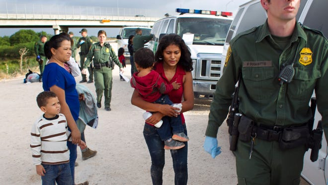 Some of a dozen women and children from Honduras are apprehended by Border Patrol near the Anzalduas International Bridge not far from the border with Mexico at the Rio Grande river in Mission, Tex., on Saturday, June 21.