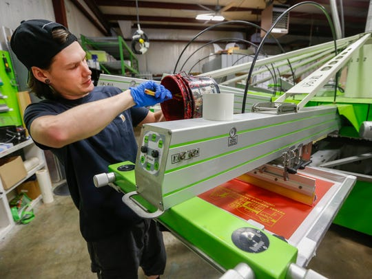 Kenneth Hall spreads ink onto an automatic screen printing