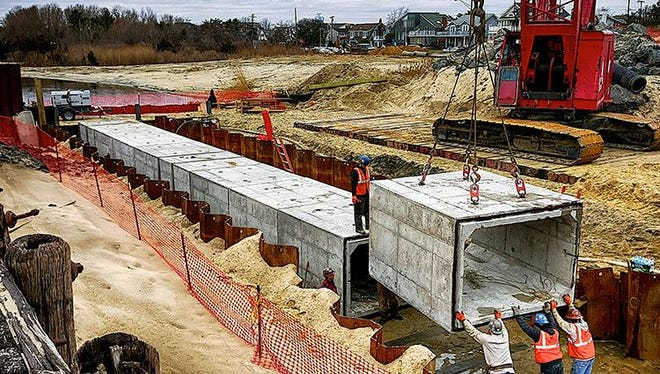 Workers put together a 600-foot-long concrete culvert in Wreck Pond. The buried tunnel will help with the lake's frequent flooding and water quality issues.