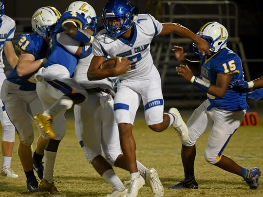 Barron Collier's Jayden Rolle (7) makes a run against Largo in the Class 6A playoffs last year. Rolle is back for the Cougars this season.