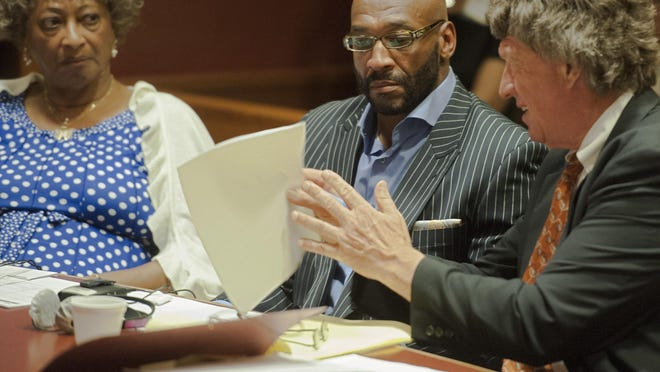 Former Philladelphia Eagles wide receiver Irving Fryar, center, and his mother, Allene McGhee,  listen to Fryar's attorney Michael Gilberti as they wait for jury selection to begin in their trial last month. Fryar and his motherwere  found guilty Friday for their role in a mortgage scam
