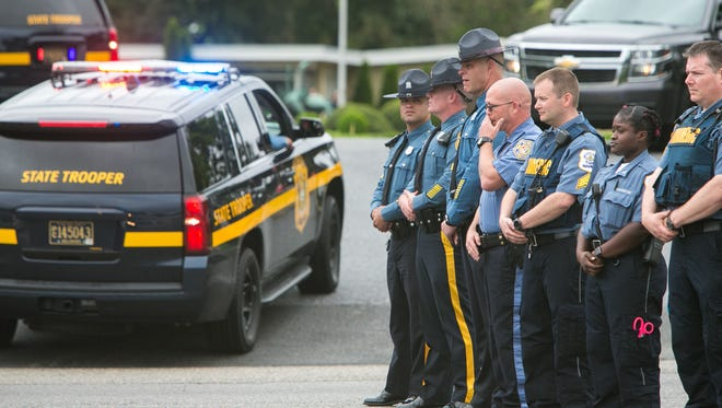 State troopers and EMS crew stand near the gate of Gracelawn Cemetery as the procession for Cpl. Stephen Ballard arrives.