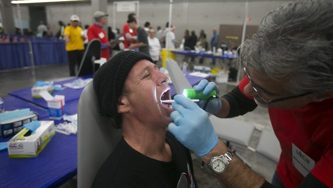 Roy Ortiz of Phoenix is examined by dentist William Balestrino during the Third annual Dental Mission of Mercy event at Veterans Memorial Coliseum in Phoenix on Dec. 12, 2014. Volunteers are sought for this year's event.