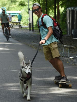 Ryan Anderson, 22, of Wappingers Falls travels on his longboard with his dog Roman at the Walkway Over the Hudson State Historic Park.