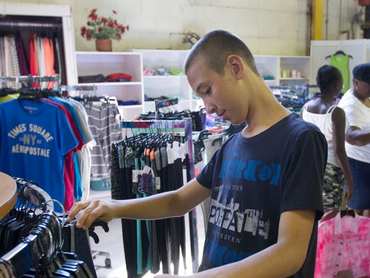 The warehouse at Ocean Co. Hunger Relief on Germania Station Rd. in Toms River offers new, designer clothing for back to school shoppers. Derek Felenczak, 14, Manchester, picks out some new clothes for school.  August 18, 2014-Toms River, NJ. Staff photographer/Bob Bielk/Asbury Park Press