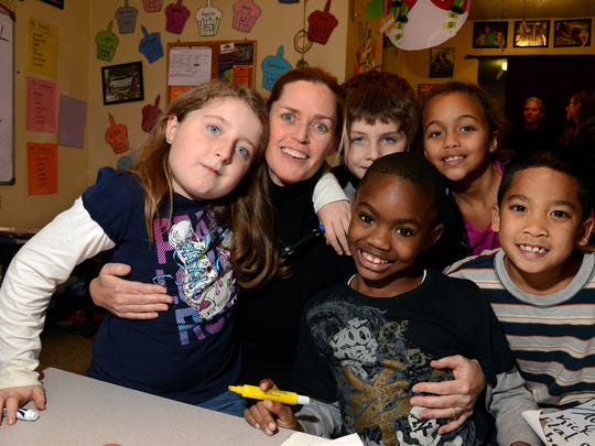 Elizabeth Brazas, president of the WNC Community Foundation, pose with a host of children at the Deaverview Learning Center on Wednesday, December 10, 2014. Ids (L to R) Ella Kimrey,v9, WNC President, Elizabeth Brazas, Quayvian Davis, 6, (sitting); Logan Kimrey, 8, (standing); Kiarra Plummer, 8, and six-year-old, Jeffery Lalita, (far right).