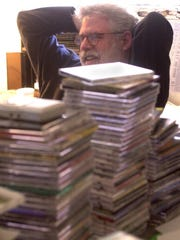 "Behind stacks of CDs, ""World Cafe"" host and creator David Dye relaxes in his WXPN office in West Philadelphia in 2002."