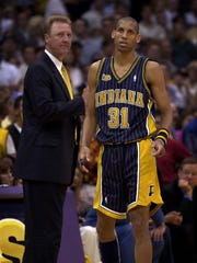Indiana Pacers' Reggie Miller looks toward the scoreboard as coach Larry Bird looks on during the closing seconds of Game 6 of the NBA Finals Monday June 19 2000 in Los Angeles.