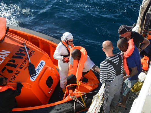 Personnel from LifeBoat, right, and the Migrant Offshore
