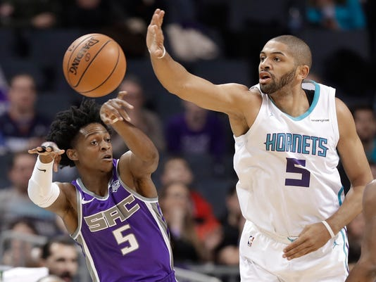 Sacramento Kings' De'Aaron Fox, left, passes the ball past Charlotte Hornets' Nicolas Batum, right, during the first half of an NBA basketball game in Charlotte, N.C., Monday, Jan. 22, 2018. (AP Photo/Chuck Burton)