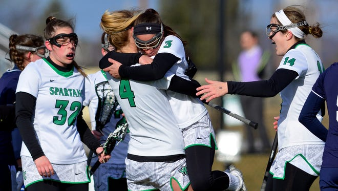 Allison Kolacy (4) of York College hugs teammate Rachel Saks after Saks scored against Messiah College in the first half, Wednesday  March 2 2016. John A. Pavoncello photo
