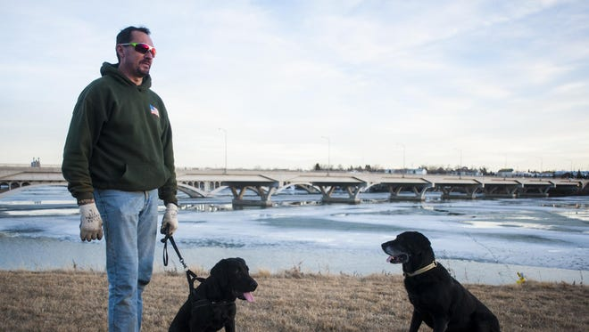 Ray Wrobel enjoys a sunset walk with his two dogs, Razzer and Vader, along the Missouri River during a day of record high temperatures Wednesday.