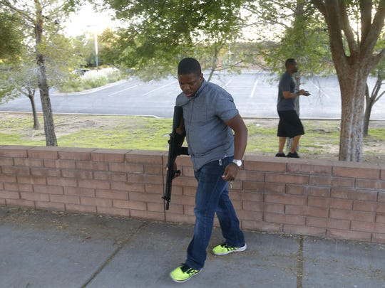 Jarvis Johnson carries an AR-15 before a Police Brutality protest in downtown Mesa on June 8, 2018.