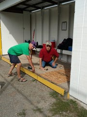 Don Scutt and Doug Arnold fix the floor in one of the