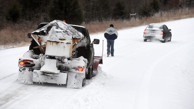 A Baxter County snow removal vehicle clears snow on Hand Cove Road while a stranded motorist walks back to his car Monday morning. The Twin Lakes Area received its first major winter weather event of the season.