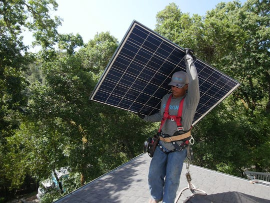A worker installs a solar panel on a house.